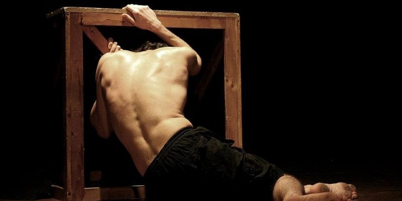 Theatrical scene: man bent over a piece of wood