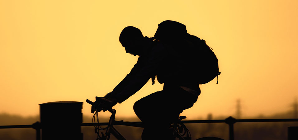 man silhouette on bicycle